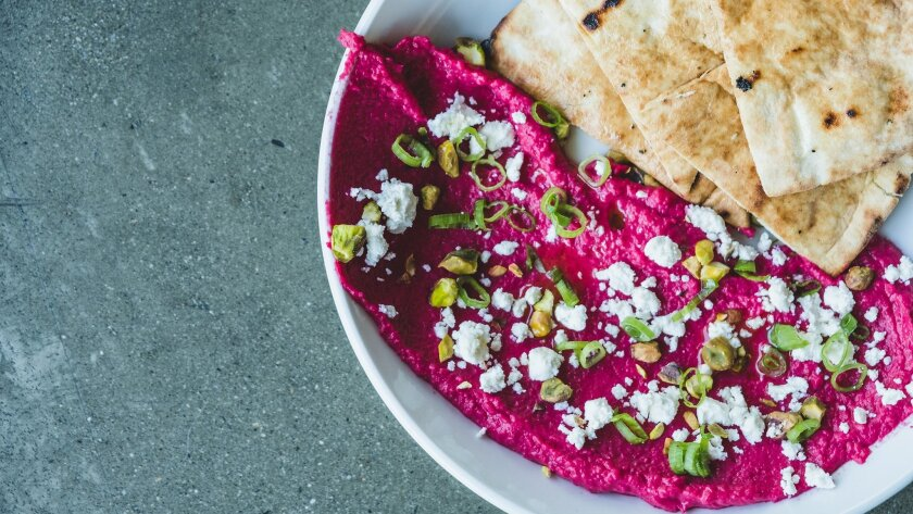 The roasted beet hummus served with pita bread, feta, toasted pistachios and green onion at Hundred