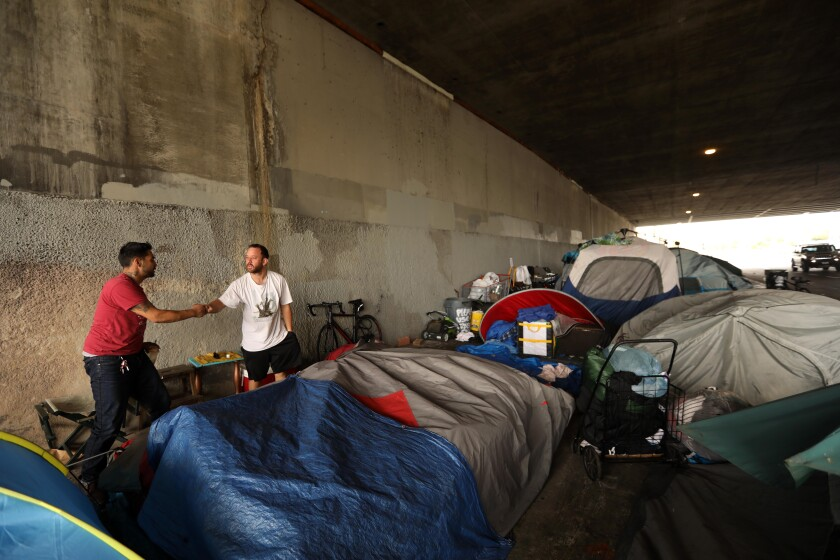 Francisco Aldana, 30, left, fist bumps a fellow homeless man where they live with around 25 other homeless people underneath the 405 Freeway on Venice Boulevard in Los Angeles.