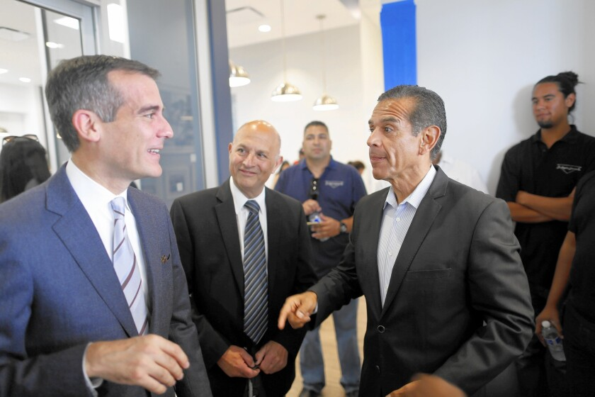 Among those at the ribbon-cutting ceremony marking the renovation of the Community Coalition's South L.A. headquarters were Mayor Eric Garcetti, left, and former Mayor Antonio Villaraigosa.