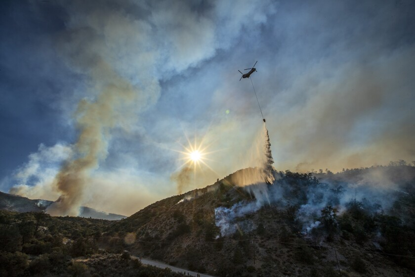 A water-dropping helicopter makes a run at the Bobcat fire in the Angeles National Forest near Llano.