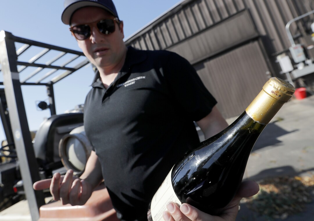 Dominic Foppoli, owner of Christopher Creek Winery and the mayor of the town of Windsor, holds a bottle of his winery's 1992 Petite Sirah that has been spoiled by the heat and smoke of the Kincade fire.