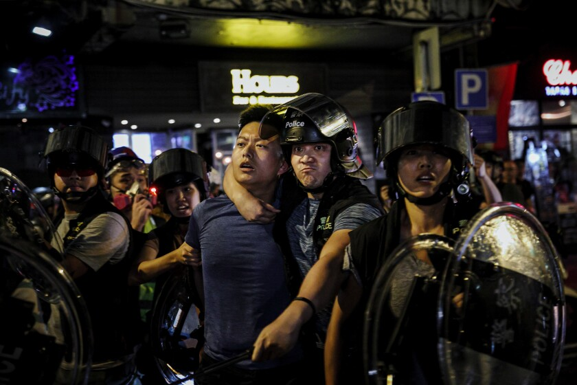 An officer in Hong Kong instructs people to step back as a man is arrested during a protest in 2019.