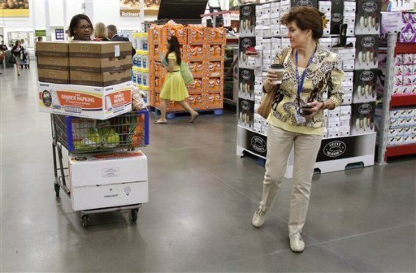 In this June 2, 2011 photo, shoppers Leslie Corridon, left, and Leslie Christon walks the aisles at a Sam's Club store in Rogers, Ark. Wholesale companies added to their stockpiles in April for a 16th straight month, a sign that businesses were confident in future sales gains. However, fresh data since then has shown the economy has weakened, suggesting supply levels could shrink in the months to come. (AP Photo/Danny Johnston)