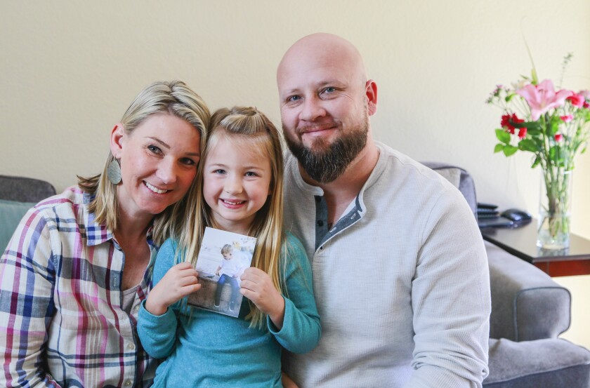 Promoting random acts of kindness in memory of their late son Blake, seen in picture, Leah Davis, left, and Rob Davis, right, and their daughter Scarlett, 5, pose for a photo in their Carmel Valley home on Jan. 7. Over the past 2-1/2 years, hundreds of people worldwide have posted on social media their good deeds #ForBlake.