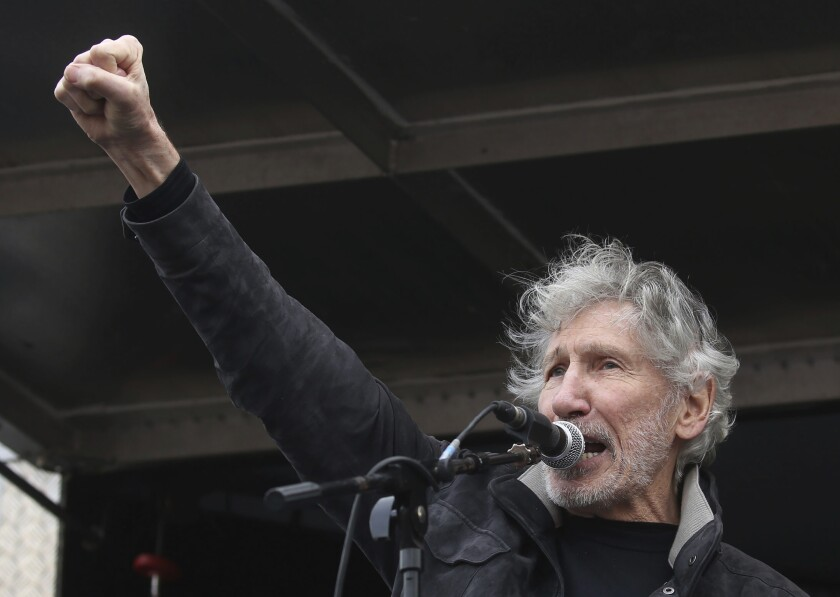 A man stands at microphone with his fist in the air.