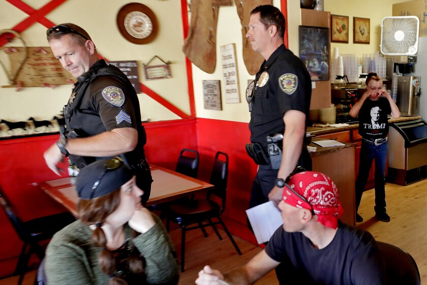 Police officers in Wickenburg, Ariz., leave the Horseshoe Cafe on May 1.