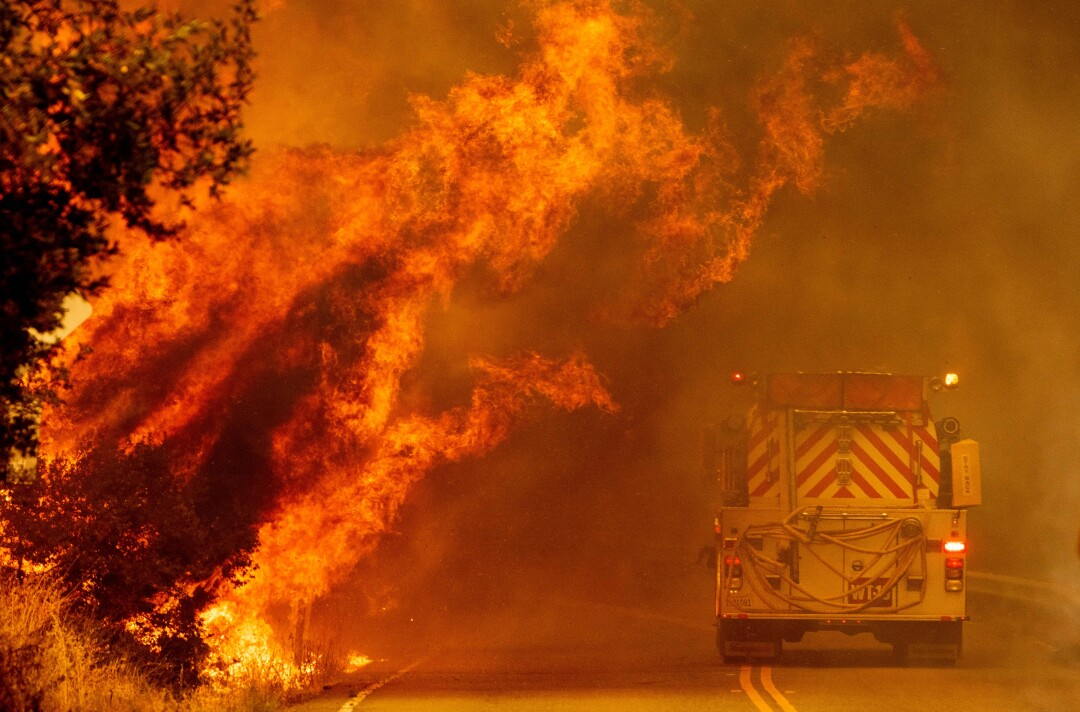 A fire truck drives through flames in Napa County.