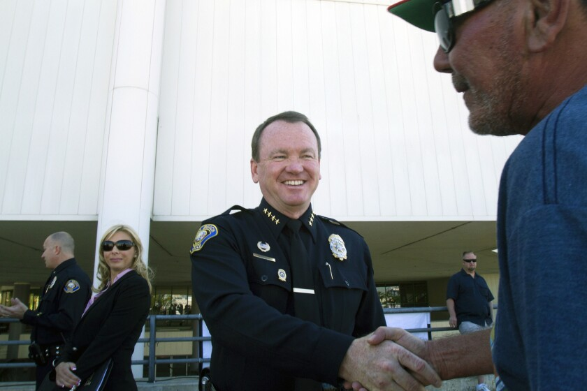 Long Beach Police Chief Jim McDonnell, center, is greeted by visitors at the Grand Prix in Long Beach.