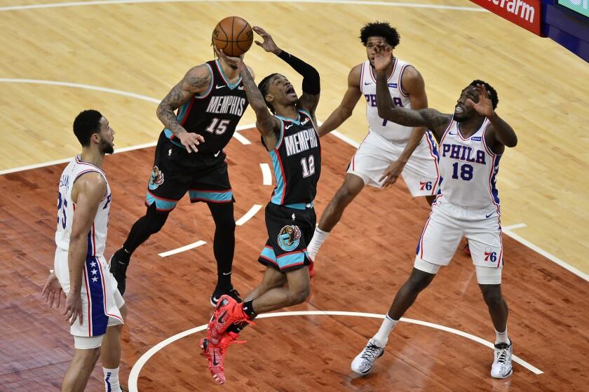 Memphis Grizzlies guard Ja Morant (12) goes to the basket next to Philadelphia 76ers guard Shake Milton (18) during the first half of an NBA basketball game Saturday, Jan. 16, 2021, in Memphis, Tenn. (AP Photo/Brandon Dill)