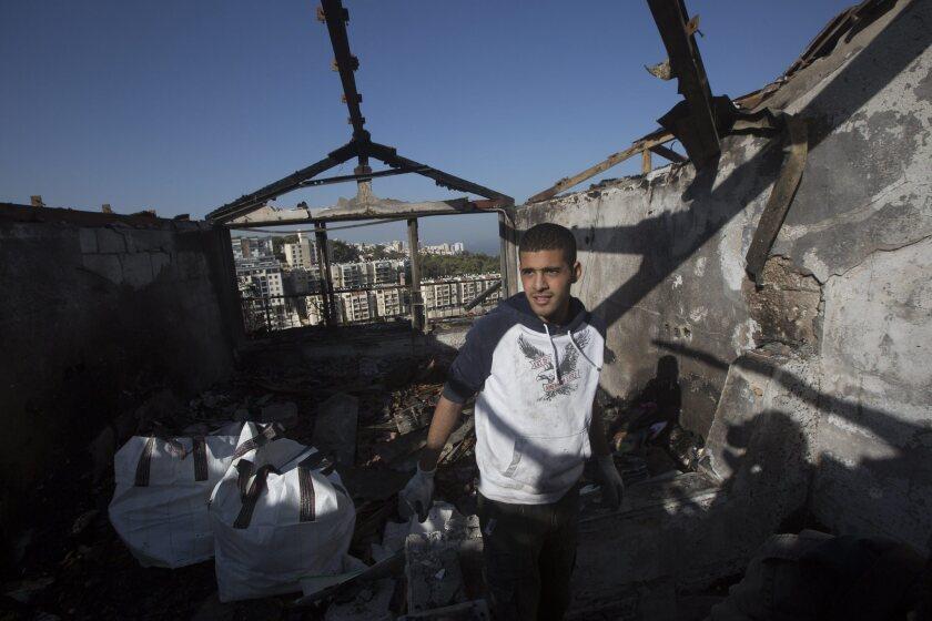 An Israeli inspects his burned house after a major fire swept the northern coastal city of Haifa.