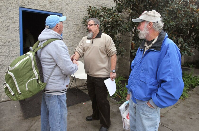 Doug Ferris, middle, the manager of new Haven House Emergency Shelter, greets Jerry Markham, at left, who hopes to get admitted to the new shelter, along with John Vezina, at right. San Diego County supervisors are considering a new comprehensive program to assist homeless people with severe mental