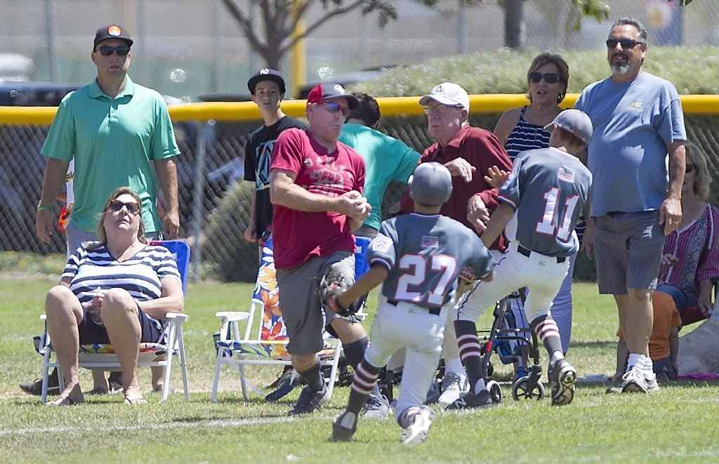 A fan catches a foul ball that would have been playable by a Huntington Valley outfielder and was met by several boos by other fans in attendance during the Little League District 62 Majors All-Stars championship game.