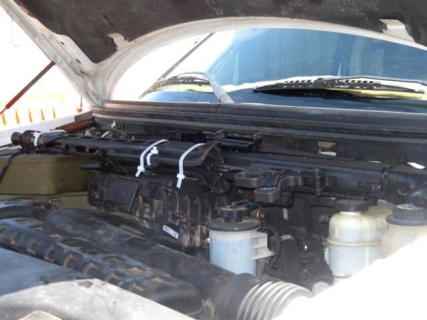 A machine gun is strapped to the engine of a Ford F-150 pickup truck stopped at a border inspection checkpoint in Andrade on Friday, July 10, 2010.