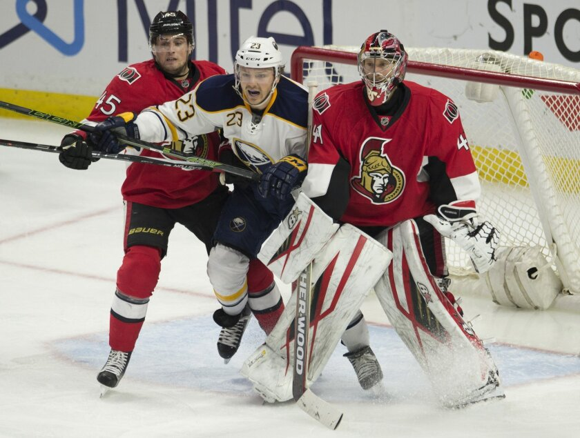 Buffalo Sabres' center Sam Reinhart (23) is sandwiched between Ottawa Senators' goalie Craig Anderson and defenseman Chris Wideman (45) during the third period of an NHL hockey game, Tuesday, Feb. 16, 2016 in Ottawa, Ontario. The Senators defeated the Sabres 2-1. (Adrian Wyld/The Canadian Press via