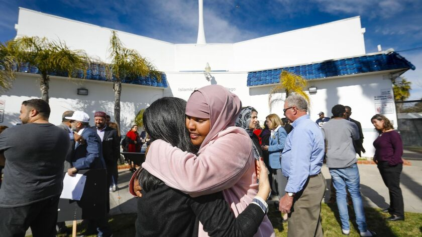 Carol Kim, left, of the San Diego Building Trades Council and Ismahan Abdullahi, right, an organizer of a news conference hosted by Muslim Leadership Council of San Diego denouncing mass shootings at two mosques in New Zealand, embrace at the Islamic Center of San Diego.