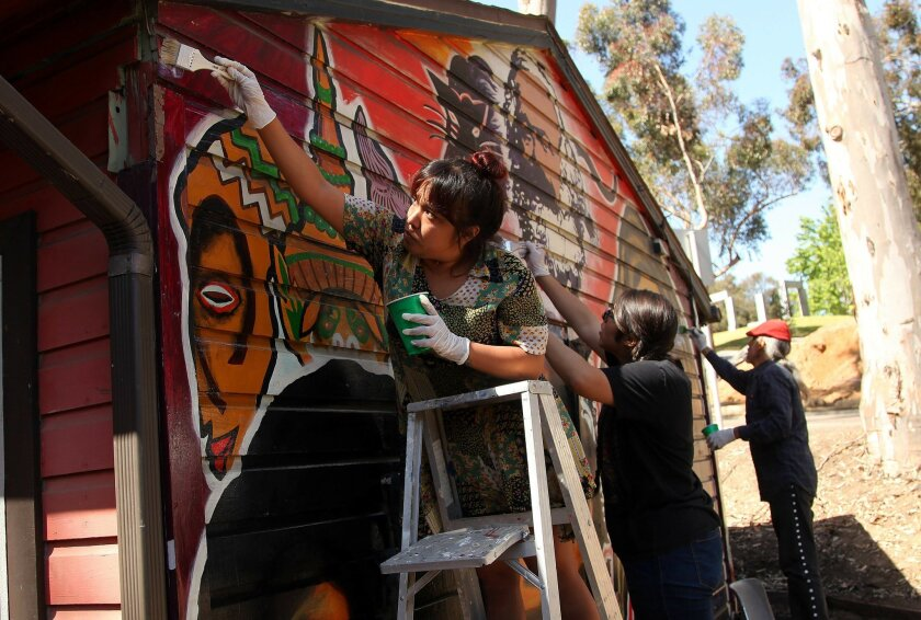Lilly Allen, left, paints the Che Cafe at UC San Diego with Fabiola Orozco and artist Mario Torero on Thursday morning.