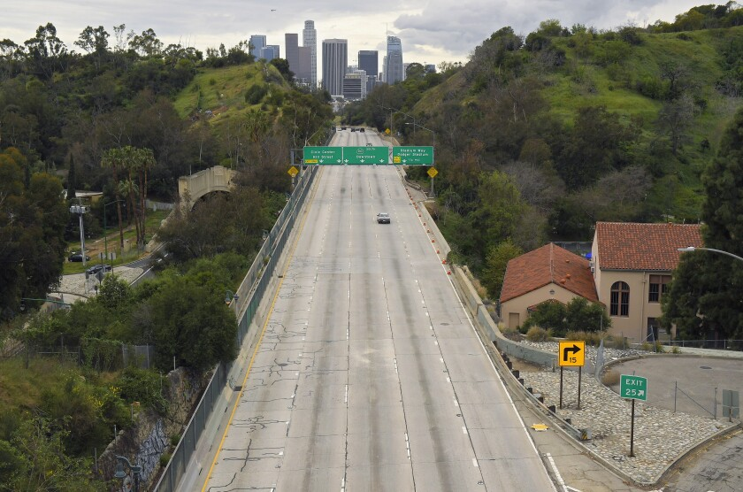 FILE - In this March 20, 2020, file photo, extremely light traffic moves in the mid-afternoon along the 110 Harbor Freeway toward downtown Los Angeles. Auto insurers are short-changing California motorists on refunds that were ordered last year because there have been far fewer motor vehicle accidents during the pandemic, the state's insurance regulator said Thursday, March 11, 2021. (AP Photo/Mark J. Terrill, File)