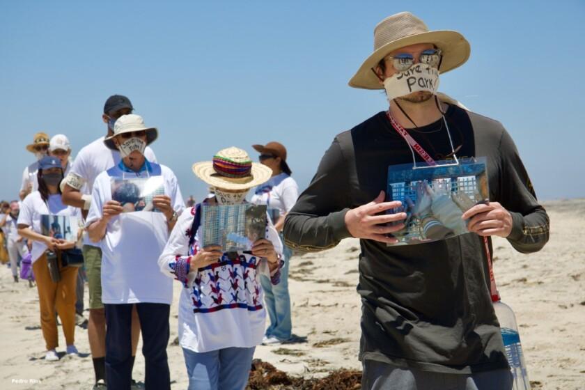 Docenas de personas caminan en silencio por la playa cerca del Parque de la Amistad el 13 de junio de 2021.