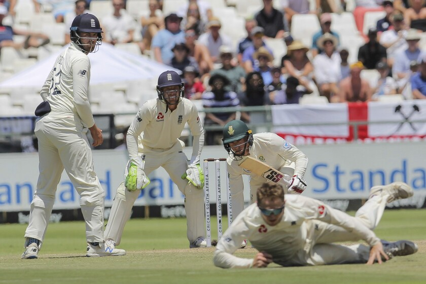 South Africa's batsman Pieter Malan along with England's wicketkeeper Jos Buttler and Dom Sibley watch at Dom bess fields the ball during day five of the second cricket test between South Africa and England at the Newlands Cricket Stadium in Cape Town, South Africa, Tuesday Jan. 7, 2020. (AP Photo/Halden Krog)