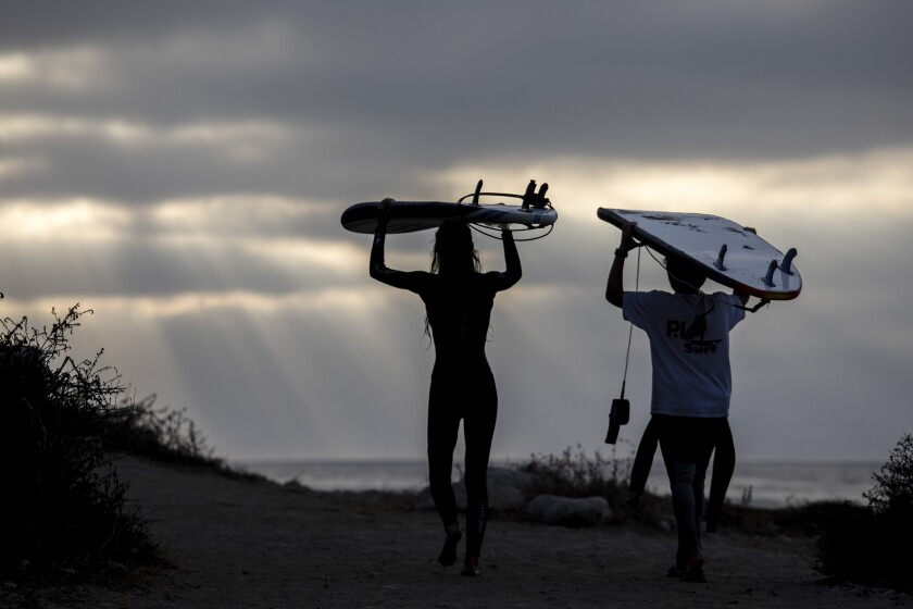 Young surfers carry their boards on their heads as they leave Rat Beach in Palos Verdes Estates earlier this week.