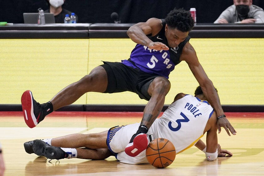 Toronto Raptors forward Stanley Johnson (5) falls over Golden State Warriors guard Jordan Poole (3) as they chasea loose ball during the second half of an NBA basketball game Friday, April 2, 2021, in Tampa, Fla. (AP Photo/Chris O'Meara)