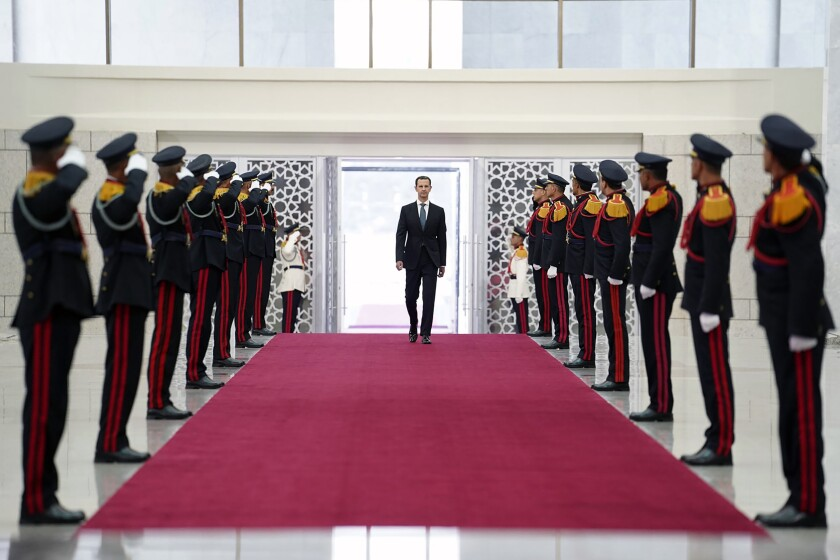 In this photo released by the official Facebook page of the Syrian Presidency, Syrian President Bashar Assad, reviews an honor guard at the Syrian Presidential Palace in the capital Damascus, Syria, Saturday, July 17, 2021. In power since 2000, Assad's re-election in a landslide was not in doubt. His new term starts with the country still devastated by the 10-year war and sliding deeper into a worsening economic crisis. (Syrian Presidency via Facebook via AP)