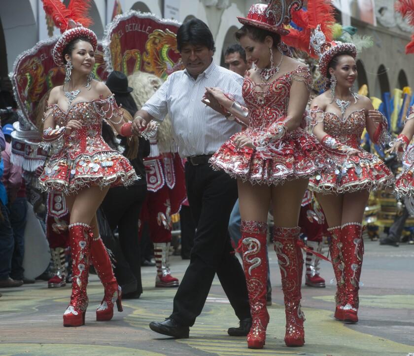 El presidente de Bolivia, Evo Morales (c), baila la danza boliviana de la Morenada junto a un grupo de mujeres que participan en el Carnaval de Oruro, la fiesta mayor del folclore boliviano declarada en 2001 Patrimonio Oral e Intangible de la Humanidad por la Organización de Naciones Unidas para la Educación la Ciencia y la Cultura (Unesco). EFE