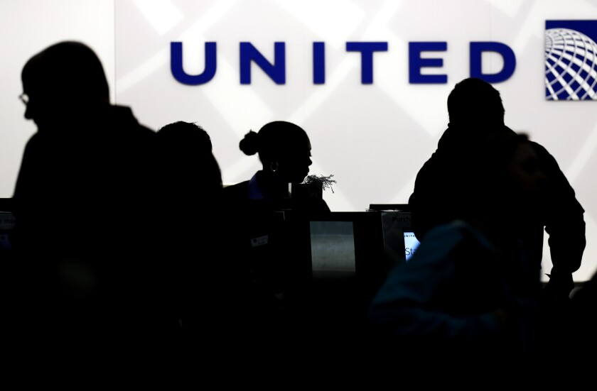 Travelers check in at the United Airlines ticket counter at Terminal 1 in O'Hare International Airport in Chicago. A computer problem led to delays Tuesday morning.