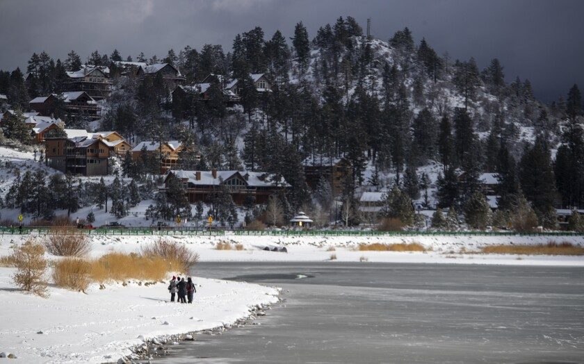 Residents and visitors walk the shore of Big Bear Lake after the first big storm of the year in December.