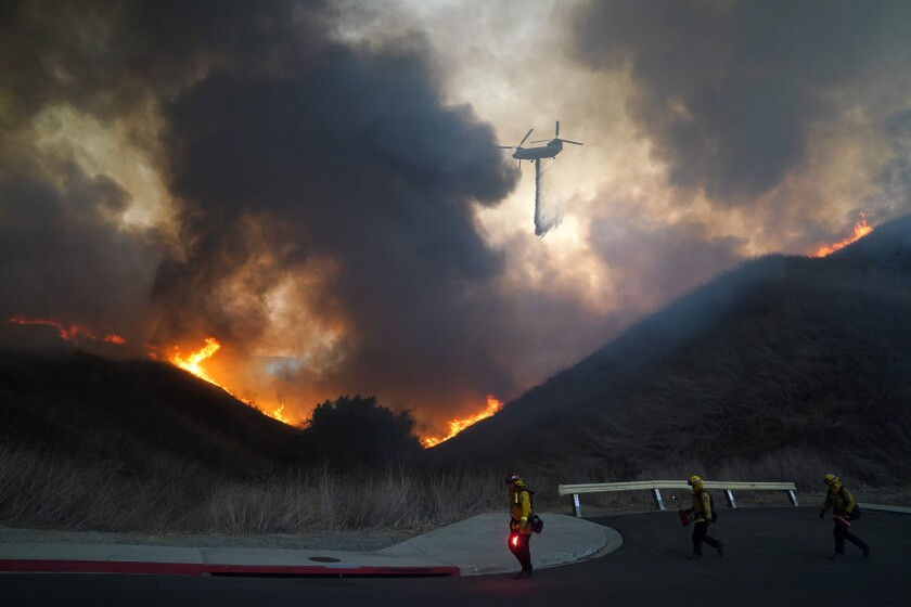 A helicopter drops water as firefighters walk with drip torches to set a backfire against the Blue Ridge Fire on Tuesday, Oct. 27, 2020, in Chino Hills, Calif. Facing extreme wildfire conditions this week that included hurricane-level winds, the main utility in Northern California cut power to nearly 1 million people while its counterpart in Southern California pulled the plug on just 30 customers to prevent power lines and other electrical equipment from sparking a blaze. (AP Photo/Jae C. Hong)
