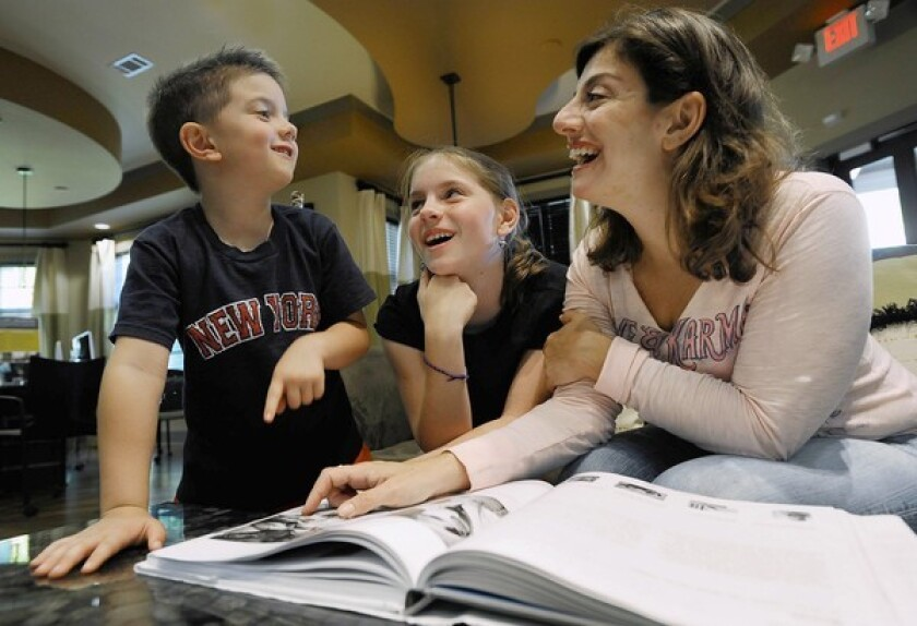Alaina Giordano looks through a picture book with her son, Bud, and daughter, Sofia, in the recreation center of their apartment building in Durham, N.C., in May 2011.