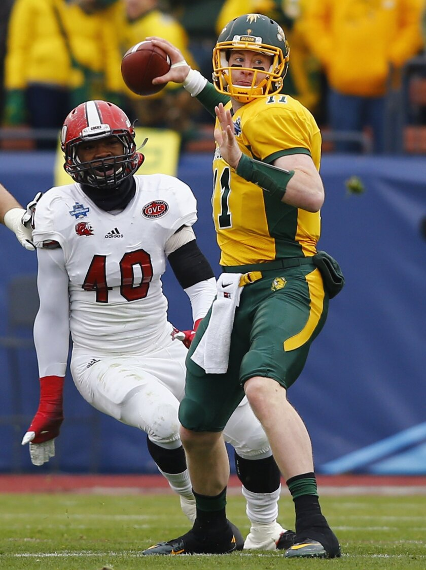 FILE - In this Jan. 9, 2016 file photo, North Dakota State quarterback Carson Wentz (11) passes as Jacksonville State defensive end Darius Jackson (40) applies pressure during NDSU's 37-10 win in the FCS championship NCAA college football game, Saturday, Jan. 9, 2016, in in Frisco, Texas. North Dak