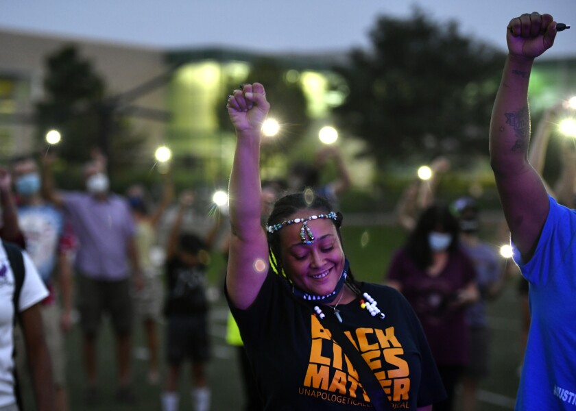 FILE - In this Aug. 23, 2020 file photo Ebony Wallace holds her fist in the air along with other participants at an event, held to honor the memory of Elijah McClain, in Denver. On Friday, Jan. 8, 2021, the Colorado attorney general opened a grand jury investigation into the death of McClain, a 23-year-old Black man who was stopped as he walked down the street, placed in a neck hold, and injected with a sedative in 2019. (Helen H. Richardson/The Denver Post via AP, File)