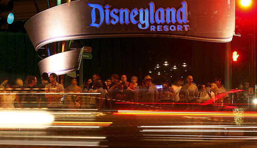 Visitors to Disneyland wait to cross Harbor Boulevard on the eastern side of the theme park in Anaheim.