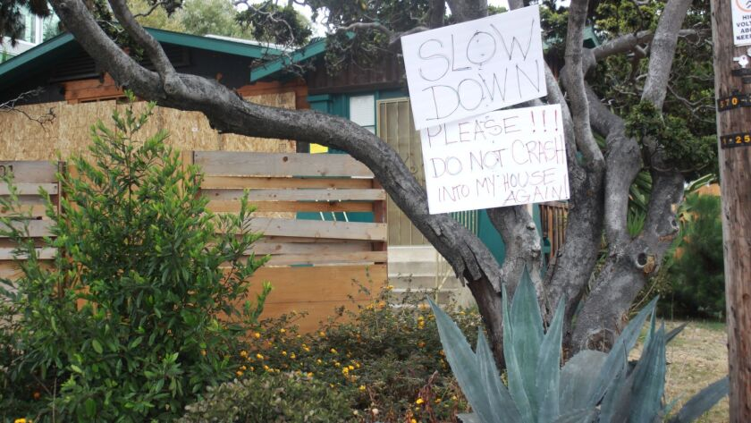 After a car crashed into this house on Torrey Pines Road at Ivanhoe Avenue, the homeowner posted advisory signs to face the thousands of cars that use Torrey Pines Road daily in La Jolla.