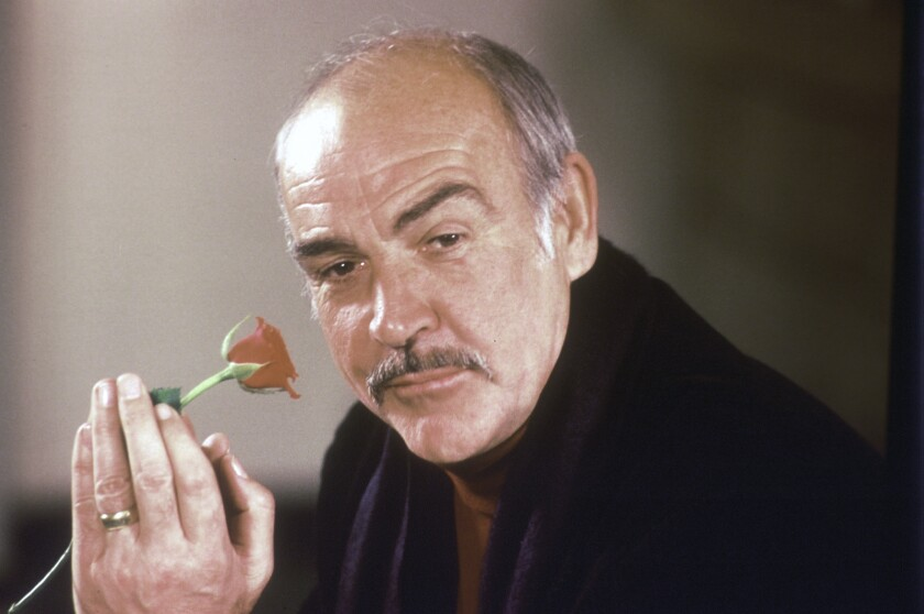 """FILE - In this Jan. 23, 1987 file photo, actor Sean Connery holds a rose in his hand as he talks about his new movie """"The Name of the Rose"""" at a news conference in London. Scottish actor Sean Connery, considered by many to have been the best James Bond, has died aged 90, according to an announcement from his family. (AP Photo/Gerald Penny, File)"""