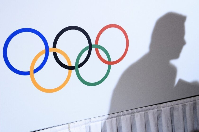 The shadow of a journalist next to the Olympic Rings during a press conference of International Olympic Committee President Thomas Bach on Dec. 08, 2016.