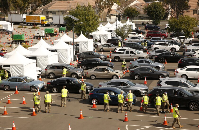 Vehicles line up at a COVID-19 vaccination site at Cal State Los Angeles.