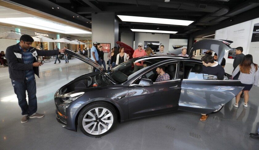 People browse the Model 3 at the Tesla showroom at the Westfield in Century City.