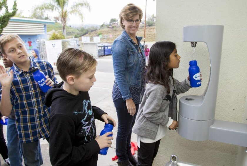 "Monte Vista Elementary School teacher Hillary Nolan looks on as 5th grader Flor Ayala fills her new reusable water bottle at the school's new ""hydration station."" The tap-styled design allows for quick and easy fill-ups."
