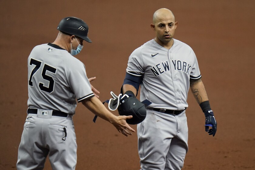 New York Yankees' Rougned Odor, right, hands his helmet to first base coach Reggie Willits after popping out against the Tampa Bay Rays during the second inning of a baseball game Sunday, April 11, 2021, in St. Petersburg, Fla. (AP Photo/Chris O'Meara)