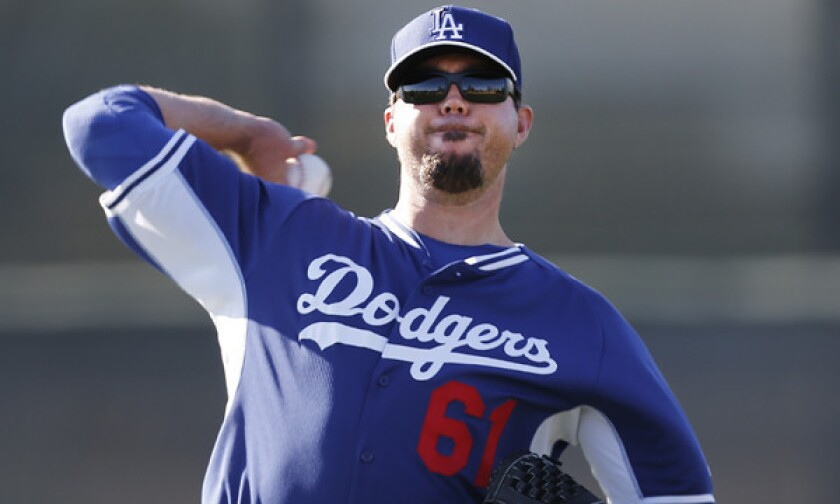 Dodgers pitcher Josh Beckett throws during a spring training practice session. A sprained thumb could force Beckett to miss his scheduled exhibition start Friday.