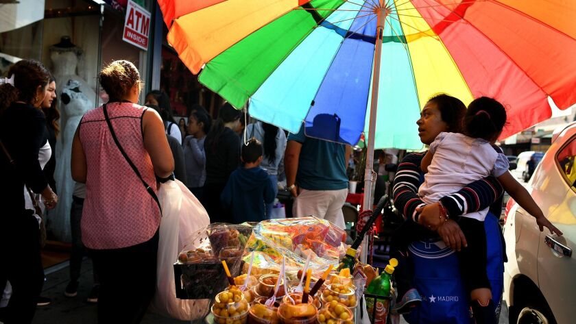 A street vendor sells food along Maple Ave. in the Fashion District in Los Angeles.