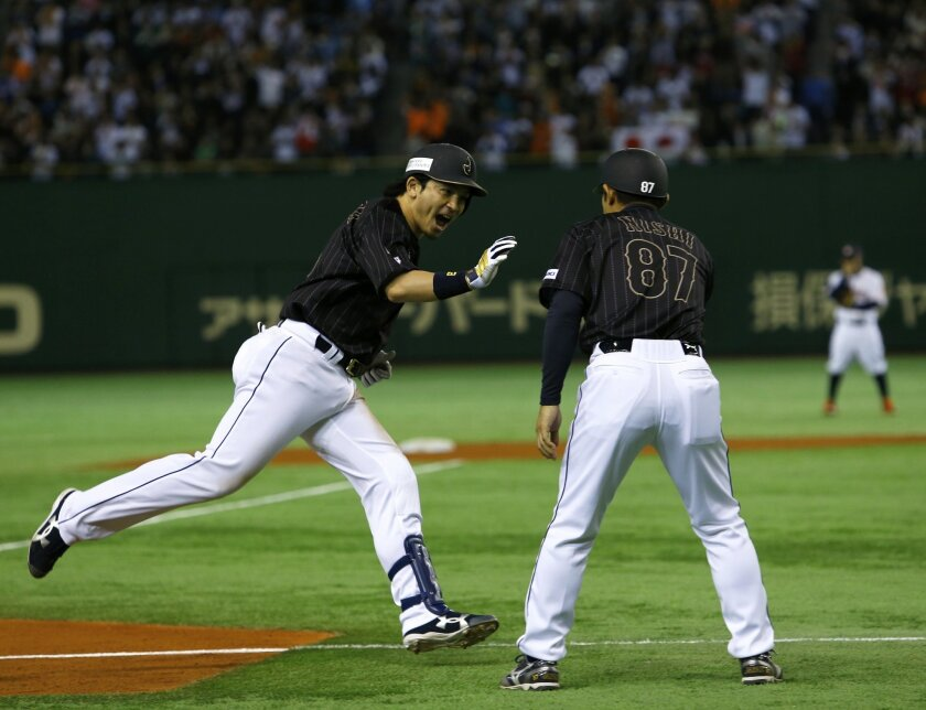 Japan's Nobuhiro Matsuda celebrates with third base coach Toshihisa Nishi as he rounds third after hitting a solo home run against MLB All-Stars in the eighth inning of Game 2 of their exhibition baseball series at Tokyo Dome in Tokyo, Friday, Nov. 14, 2014. (AP Photo/Toru Takahashi)