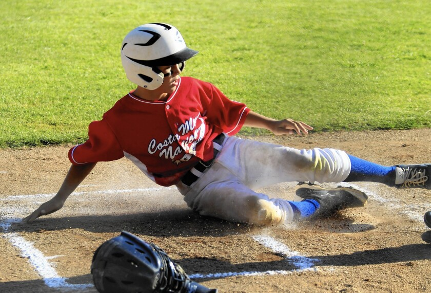 Costa Mesa National Little League's Grant L'Heureux slides into home during a 2014 game at TeWinkle Middle School, one of the city's locations with permanent lighting.