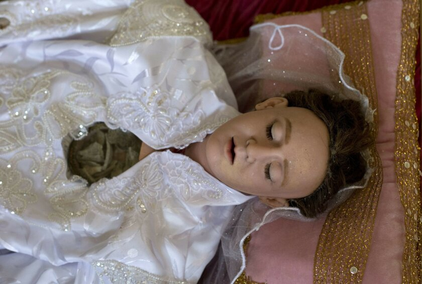 A molded wax and cloth figure of Saint Felicitas of Rome, with a glass window embedded in the chest to reveal bone fragments, lies inside a display case at the Metropolitan Cathedral in Mexico City, Friday, July 8, 2016. High definition digital x-ray technology is giving researchers in Mexico their first glimpse at the interiors of centuries-old life-size religious reliquaries representing Catholic saints. (AP Photo/Rebecca Blackwell)