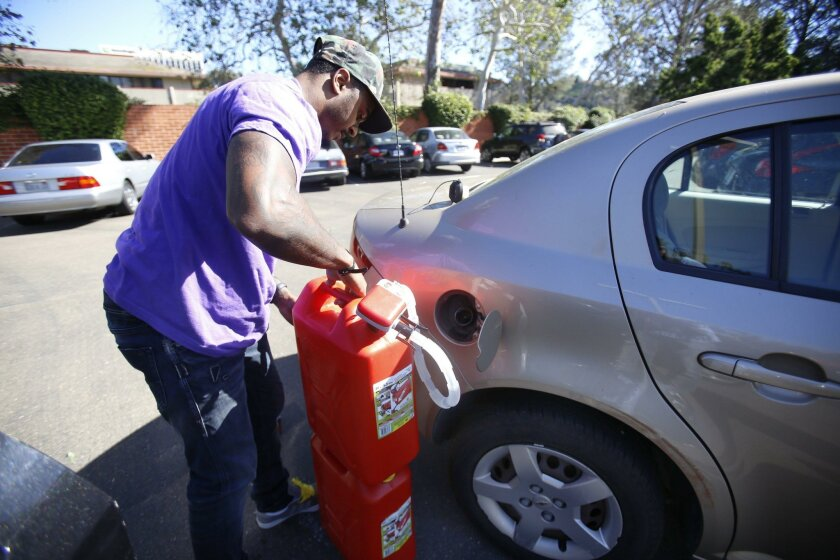 The Purple app delivers gasoline to your location. Courier Randy Harvey delivers 10 gallons of gasoline using fuel cans.