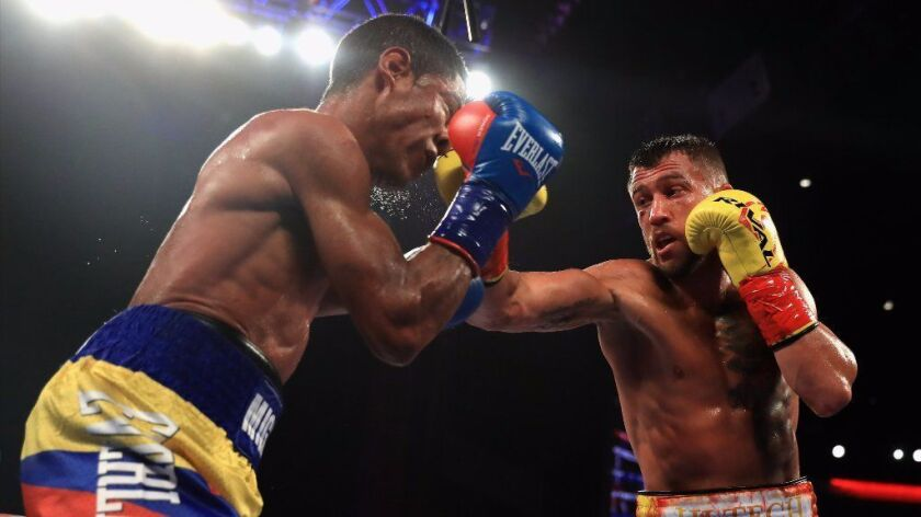 Vasyl Lomachenko and Miguel Marriaga, left, exchange blows during their WBO super-featherweight titl