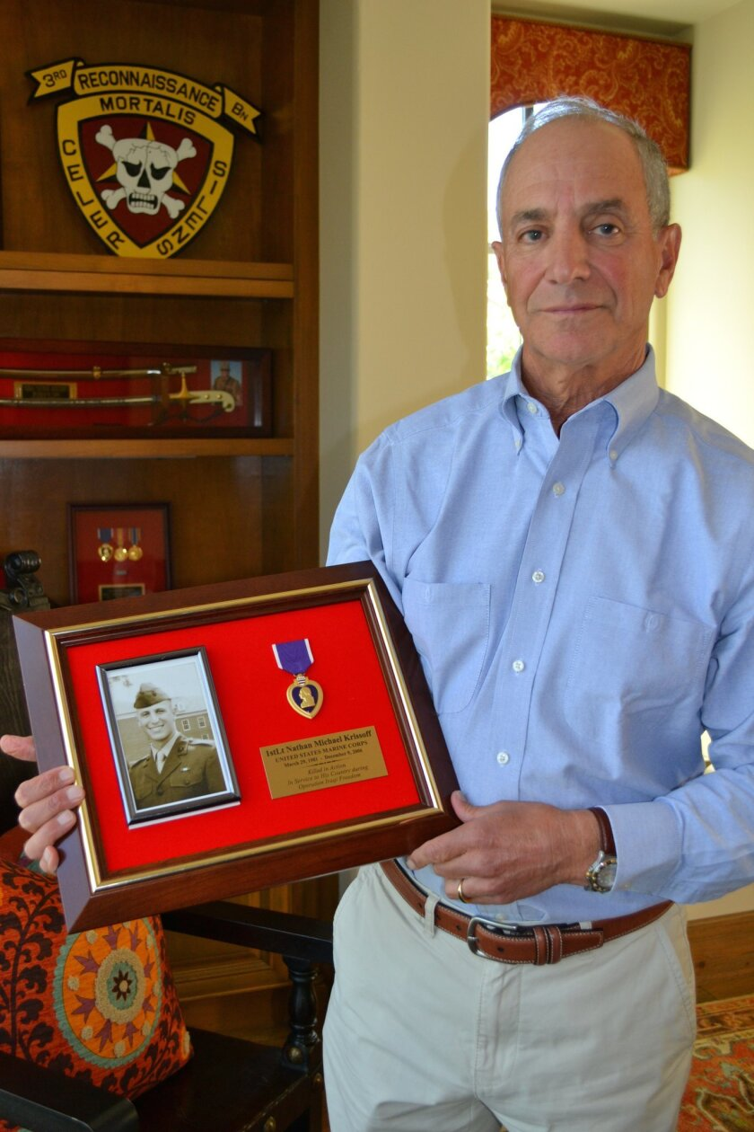 In his study in Rancho Santa Fe, Dr. Bill Krissoff holds a photo of his son 1st Lt. Nathan Krissoff and his Purple Heart medallion.