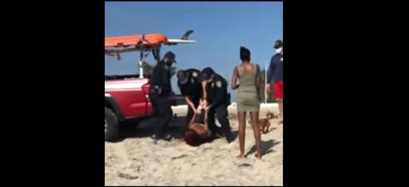An image from video shows a woman being arrested in Ocean Beach after walking her unleashed dog on the sand May 1.